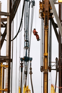 A worker abseils down the 180ft high drilling derrick on the Jack Ryan drill ship, which worked in block 31, Angola. (photo courtesy of BP p.l.c.)